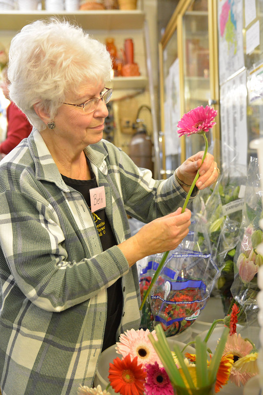 Beth Manthei slides tubing on the stem of a Gerbera daisy for supporting the head after a shipment of flowers arrives at Annie Greenthumbs Wednesday. Valentines day is one of the busiest times in the year for the floral shop, which hires part-time help to keep up with the demand.
