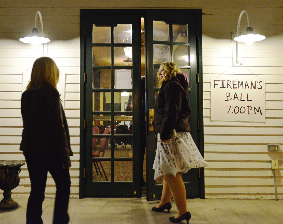 Samantha Levi opens the door as another guest approaches during the annual Fireman's Ball outside of the Sheridan Inn Saturday night. The fundraising event was to benefit the Sheridan Fire-Rescue firehouse.