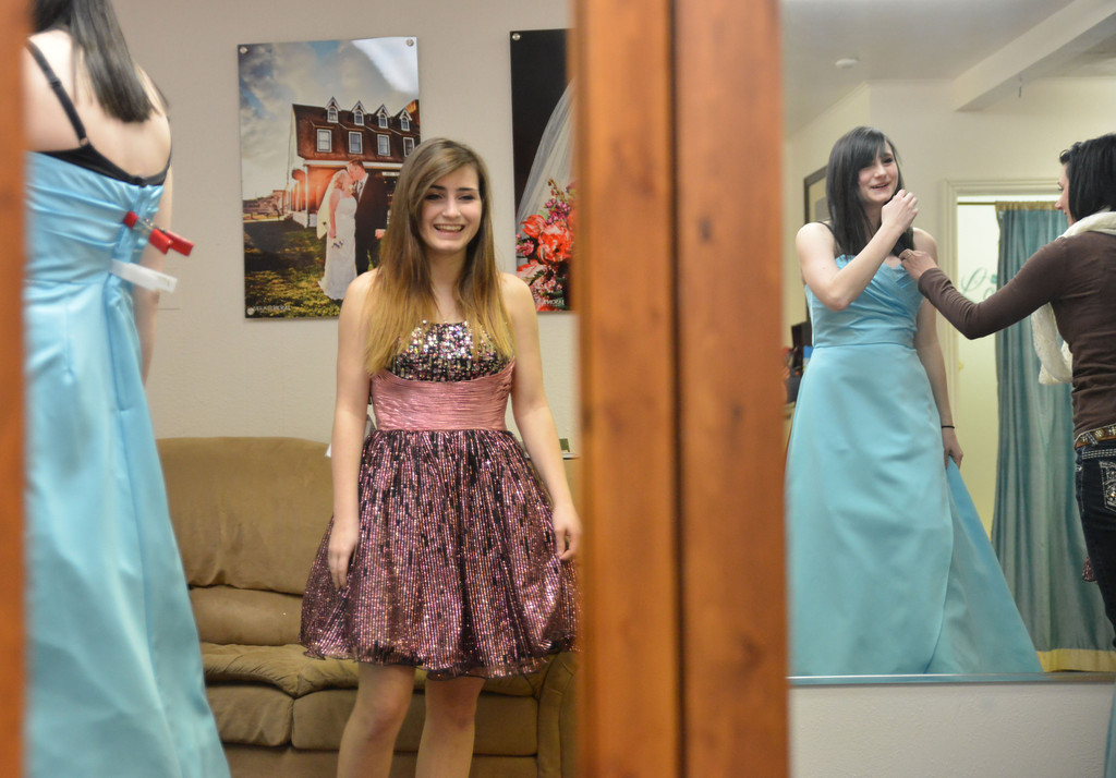 Sheridan High School sophomore Heide Rader, left, and her sister Paige Rader, a senior, look at themselves in the mirrors as they try on dresses for prom Tuesday afternoon at One Step Closer Boutique. The Sheridan High School Prom is April 5.