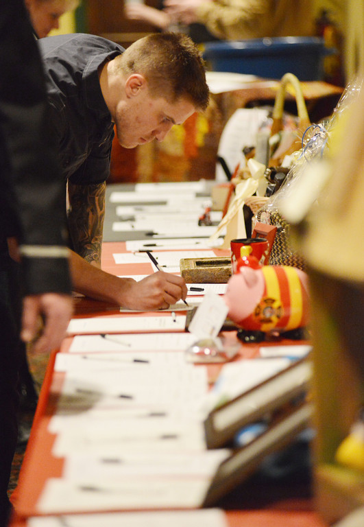 John Bublich places a bid on a Harley Davidson raffle ticket on the silent auction Saturday night during the annual Fireman's Ball at the Sheridan Inn.