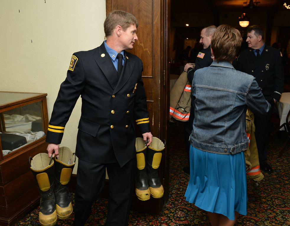 Sheridan fireman Gary Harnish carries a pair of boots into the ballroom as last-minute decorations are placed during the annual Fireman's Ball at the Sheridan Inn Saturday night.