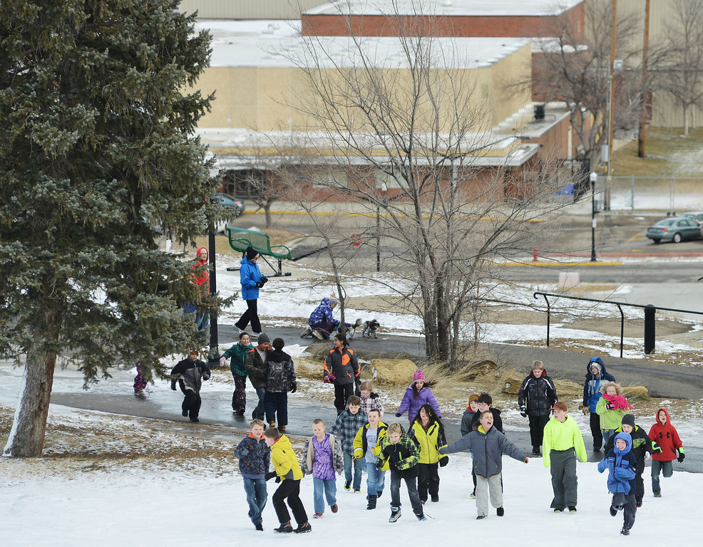 "Dozens of children run up the hill from the YMCA to go sledding below Kendrick Mansion Friday afternoon. Almost a hundred children were given sleds purchased by Century 21 BHJ Real Estate after spending most the afternoon sledding on Kendrick hill and eating hotdogs. Century 21 BHJ Realty owner Bruce Garber expressed that he wanted to celebrate the spirit of the Olympics in Sheridan, since Century 21 is the sponsor of the US men's and women's Bobsled and Skeleton teams at the 2014 Olympics. ""It's all about seeing the kids smile."" Garber said."