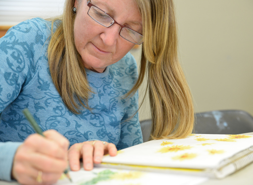Cameo Passini draws in her sketchbook during 'Beyond Sketching: Renderings in Colored Pencil with Dean States' Wednesday afternoon at the Sheridan Community Art Center in the Historic Train Depot on Fifth Street. The colored pencil workshop is one of many offered throughout the week at the Community Art Center.