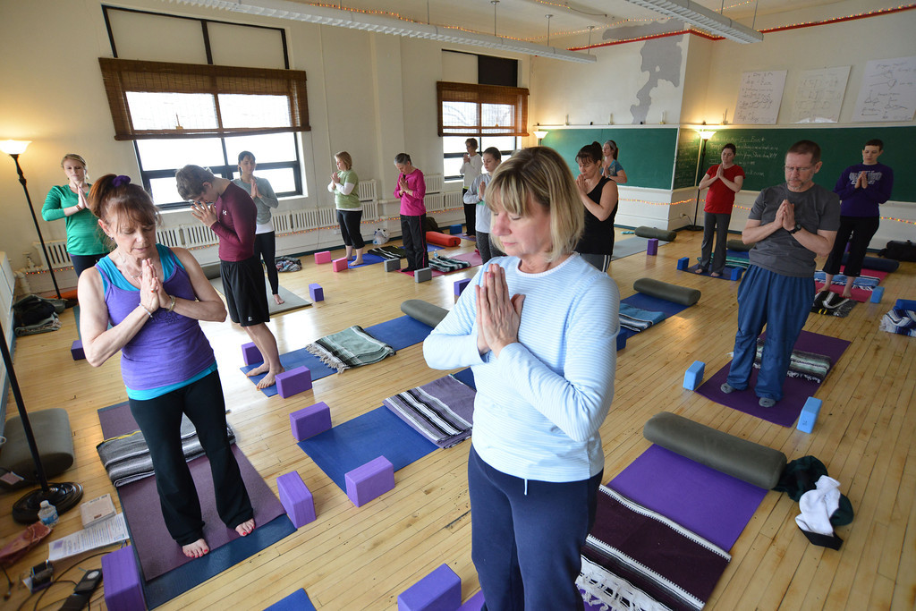 Yoga instructor Teddy Araas, left, begins the Vinyasa Yoga session with Deb White, middle, during the Free Day of Yoga and Meditation Saturday at the Old Taylor School building. The Santosha Yoga classroom was open to the public all day Saturday for those interested in trying yoga and meditation.