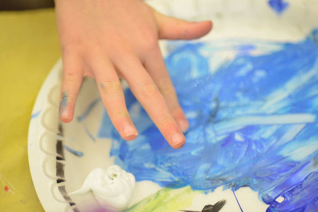 A young artist plays with the paint in her palette.