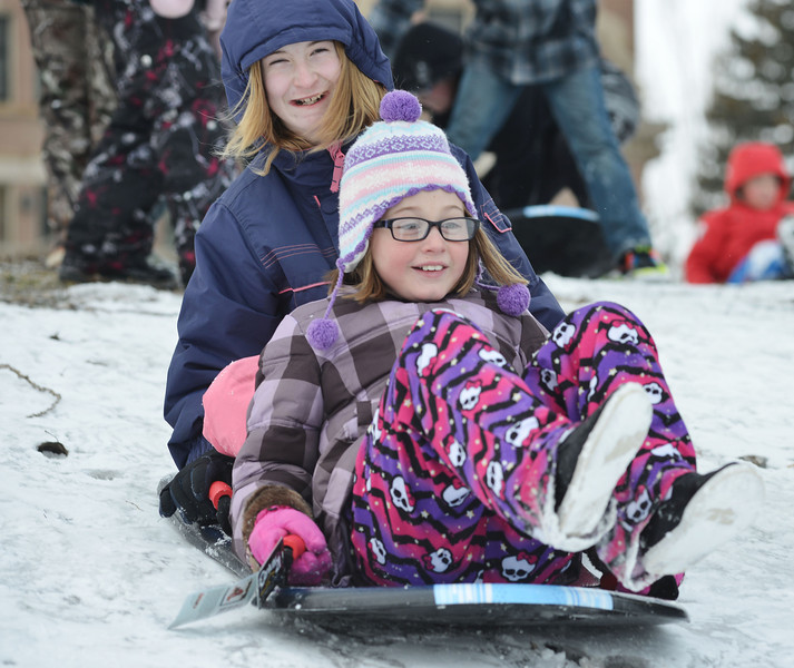 "Alexis Bates, left, and Rylie Dilmore start their ride Friday afternoon on Kendrick hill. Almost a hundred children were given sleds purchased by Century 21 BHJ Real Estate after spending most the afternoon sledding on Kendrick hill and eating hotdogs. Century 21 BHJ Realty owner Bruce Garber expressed that he wanted to celebrate the spirit of the Olympics in Sheridan, since Century 21 is the sponsor of the US men's and women's Bobsled and Skeleton teams at the 2014 Olympics. ""It's all about seeing the kids smile."" Garber said."