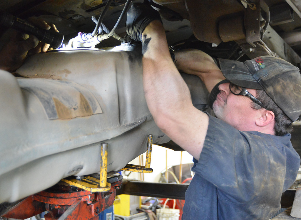 Lead Technician Jim Crawford disconnects the wires from the fuel module on a gas tank under a Ford F-150 Thursday at Welty's Auto Service on Big Goose Road. The gas tank has to be removed to be able to replace a faulty fuel pump. Welty's Auto has been in business since 1979; Dan Reinke purchased the shop in 2006 from Rex Welty and has been running the business.