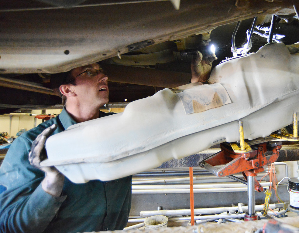 Shop owner Dan Reinke shines a flashlight on the fuel module on the gas tank of a Ford F-150 Thursday at Welty's Auto Service on Big Goose Road. The gas tank has to be removed to be able to replace a faulty fuel pump. Welty's Auto has been in business since 1979; Reinke purchased the shop in 2006 from Rex Welty and has been running the business.