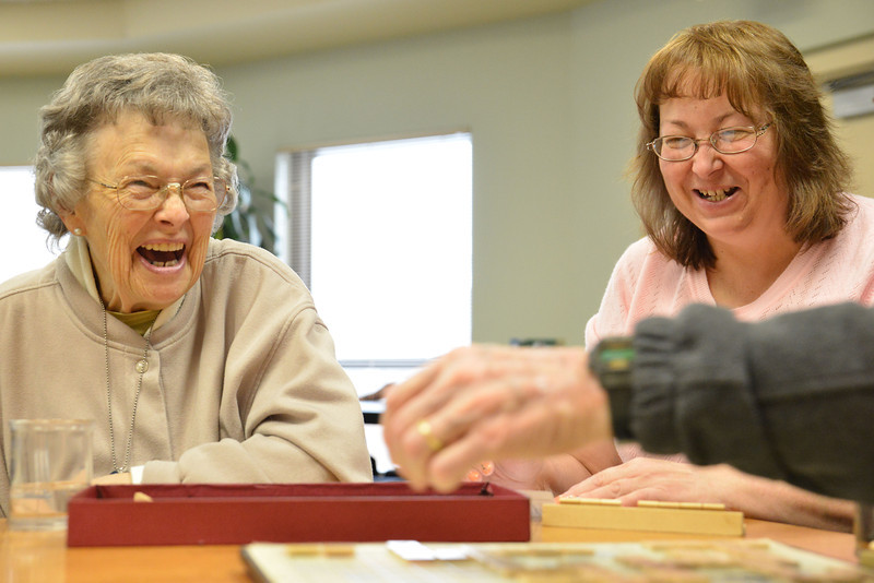 Jeanne Boe, left, and Day Break staff Dee Fairbank laugh as another player makes a clever move earning a point multiplier in the corner of the Scrabble Board Friday morning at Day Break in the Sheridan Senior Center. The word was, 'MEAN.'