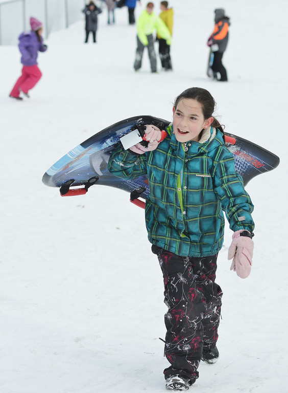 "Braedenn O'Leary, 10, climbs back up the hill with a sled to hand off to the next person waiting Friday afternoon on Kendrick hill. Almost a hundred children were given sleds purchased by Century 21 BHJ Real Estate after spending most the afternoon sledding on Kendrick hill and eating hotdogs. Century 21 BHJ Realty owner Bruce Garber expressed that he wanted to celebrate the spirit of the Olympics in Sheridan, since Century 21 is the sponsor of the US men's and women's Bobsled and Skeleton teams at the 2014 Olympics. ""It's all about seeing the kids smile."" Garber said."