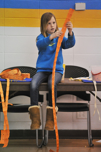 Brook Larsen, 8, attends to the 50/50 ticket table Friday night during the Sheridan Broncs' game at the Golden Dome on the Sheridan College campus. Half of the jackpot from the ticket sales goes to a luck winner, the other half goes to the Sheridan High School Booster Club.