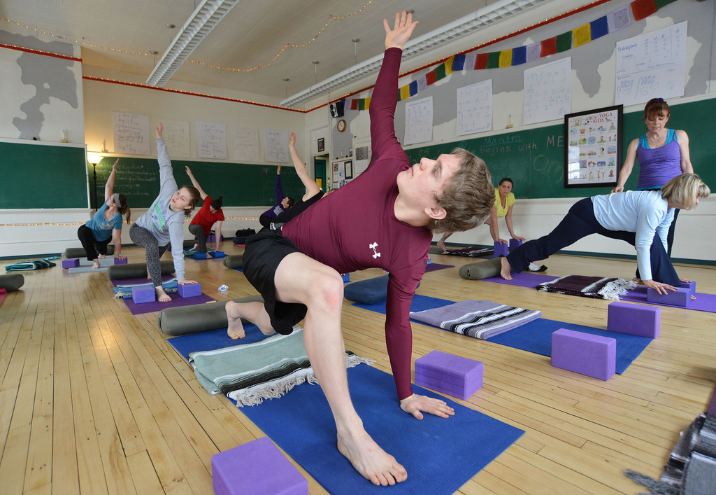 Zach Vaira holds an arm outstretched as they repeat the instructor's lesson during the Free Day of Yoga and Meditation Saturday at the Old Taylor School building. The Santosha Yoga classroom was open to the public all day Saturday for those interested in trying yoga and meditation.