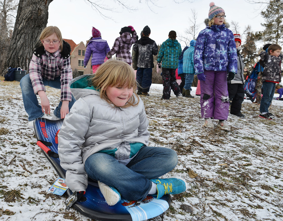 "Madison Adonis, left, and Paige Strobbe, both 9, get ready to ride the slope Friday afternoon on Kendrick hill. Almost a hundred children were given sleds purchased by Century 21 BHJ Real Estate after spending most the afternoon sledding on Kendrick hill and eating hotdogs. Century 21 BHJ Realty owner Bruce Garber expressed that he wanted to celebrate the spirit of the Olympics in Sheridan, since Century 21 is the sponsor of the US men's and women's Bobsled and Skeleton teams at the 2014 Olympics. ""It's all about seeing the kids smile."" Garber said."