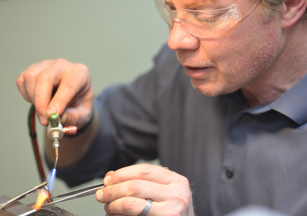 Darin Olson heats up a ring with a small torch to remove the head Tuesday at On The Rocks Jewelry. Olson will set a new stone with a new head for an order. The business opened in June of 2010 with the intention to be just a diamond broker, but the business has since expanded to offering services, repairs, sizing, setting, and custom engraving. The Sheridan Press/Justin Sheely.