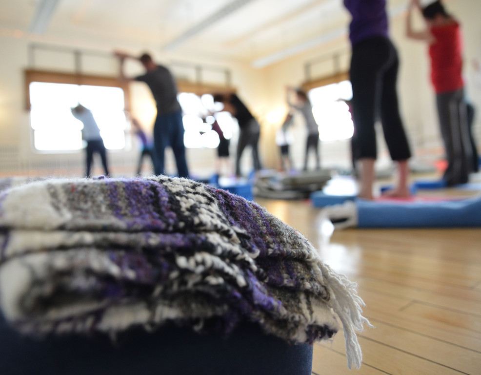 A folded blanket sits on the floor as the free Vinyasa Yoga session continues on.
