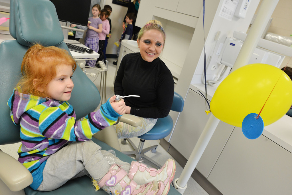 Highland Park kindergartener Cera Williams blows air at a balloon with a dental tool as student Kristen Pourroy looks on during the circus themed tour of the Dental Hygiene Department Thursday at Sheridan College. The Dental Hygiene students hosted kindergarten classes from Sheridan County to commemorate National Children's Dental health Month. The Dental Hygiene Department also sought to help the youth to become familiar with the dental office and equipment so they can feel more comfortable around them.