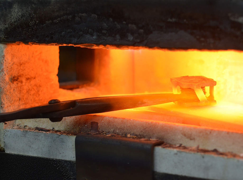 A billet of non-iron metals stacked between a temporary welded jacket is heated up in a gas forge during the Wyoming Artist Blacksmiths 'Winter Forge-in' Saturday at Bomar's Shop on Leopard Street in Sheridan. After the billet reaches the right temperature it will be removed then pressed.