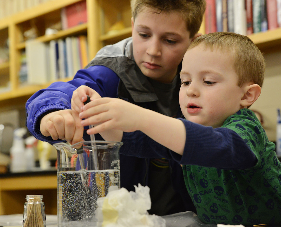 Ethan McGill, 8, and his 3-year-old brother Jason McGill fill dropper with water for a water race during the 'Water Olympics' themed Science Saturday at the Sheridan College Science Center.