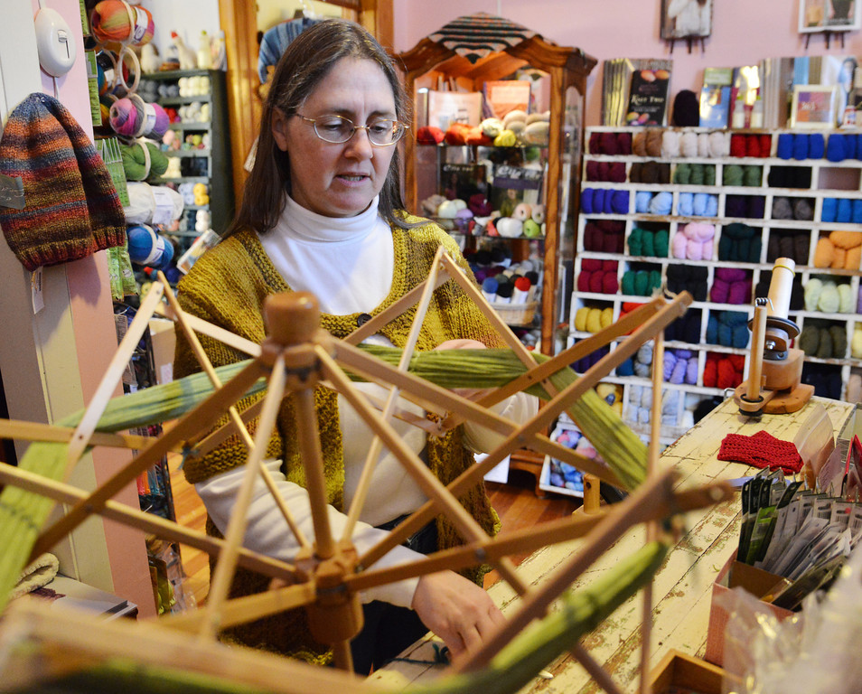 Donna Stubbs prepares a skein of yarn over a swift and pulls the lead to the ball winder Thursday at the Fiber House on Coffeen Avenue. Yarn is typically sold in skeins; the Fiber House spins them into balls for customer use.