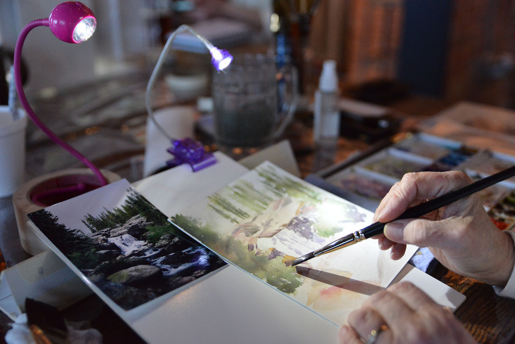 An artist uses reading lights to see her work during the Wyoming Watercolor Society's Art in Motion Friday night at the yet-to-be-named corner bar at Fifth Street and Main. Several arts painted for patrons to observe and sold pieces to fund the Watercolor society.
