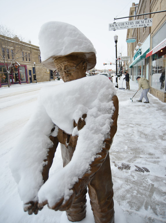A public arts sculpture remains covered in snow accumulation as business owners shovel the sidewalks on Main Street Tuesday morning in downtown Sheridan.