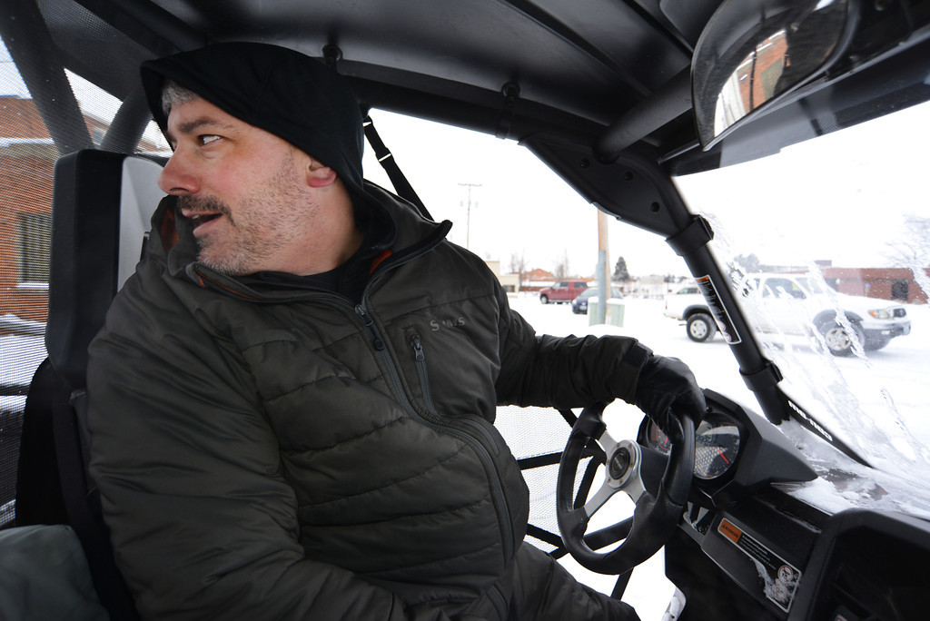 Owner of Fly Shop of the Bighorns Roger Miller looks over his shoulder as he backs up his Can-Am Commander with snowplow in the back parking lot on Brooks Street Tuesday morning.