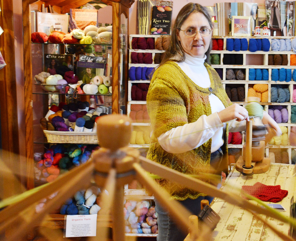Donna Stubbs spins the yarn into a ball on the ball winder Thursday at the Fiber House on Coffeen Avenue. Yarn is typically sold in skeins; the Fiber House spins them into balls for customer use.