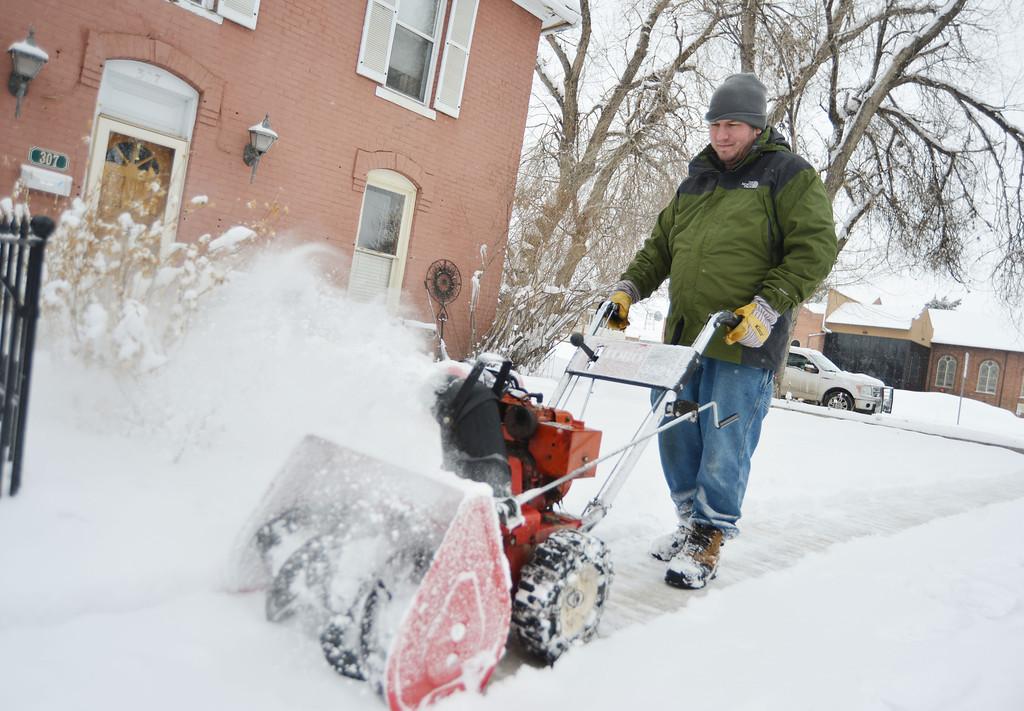 Kim Ostermyer runs a snow blower in his neighborhood Friday morning on South Thurmond Street.