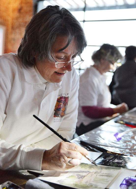Paulette Kucera paints during the Wyoming Watercolor Society's Art in Motion Friday night at the yet-to-be-named corner bar at Fifth Street and Main. Several arts painted for patrons to observe and sold pieces to fund the Watercolor society.