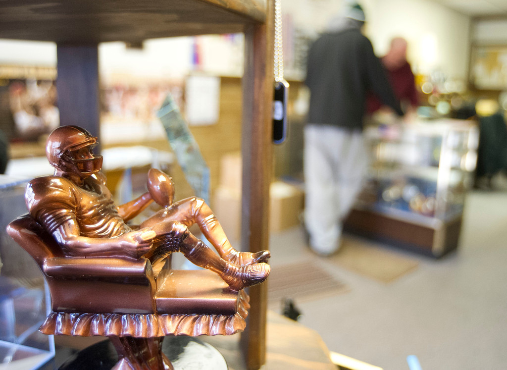A display trophy sits on display as the owners deal with a customer Thursday at The Trophy Case business on Main Street.