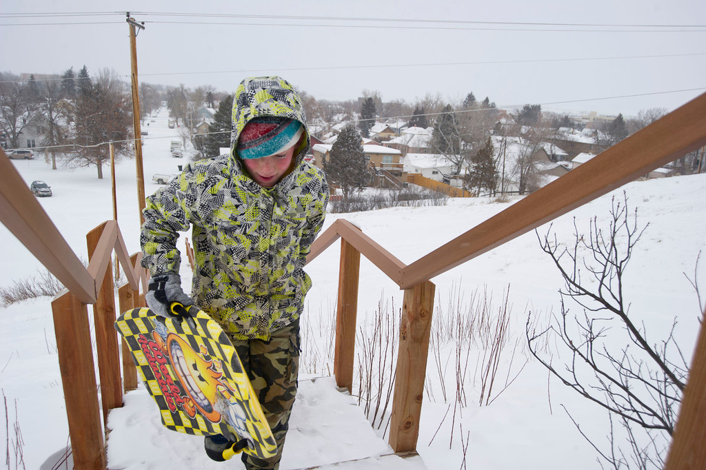 Ian Taylor, 10, climbs the stairs leading up Linden Hill with his sleds in tow Saturday.