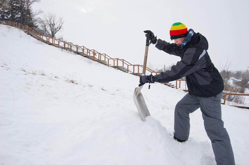 Zacary Fettig, 10, builds a snow ramp for jumping on his skis Saturday on Linden Hill.
