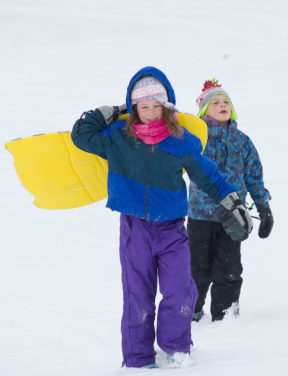 Elayna Taylor, left, leads 8-year-old Cameron Perez up the snow-covered slope to with her sled Saturday afternoon on Linden Hill.