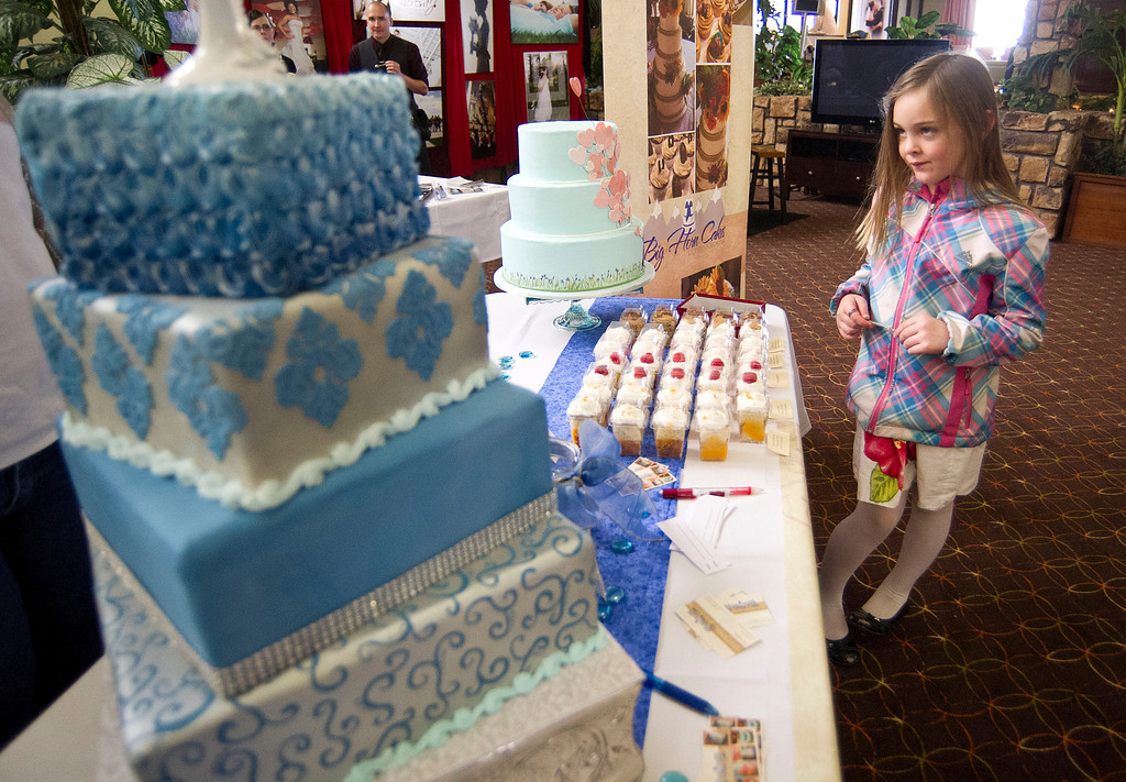 Isabella Walton, 6, sheepishly approaches a vendor for a second cake sample during the Wyoming Weddings free bridal expo Saturday at the Holiday Inn atrium.