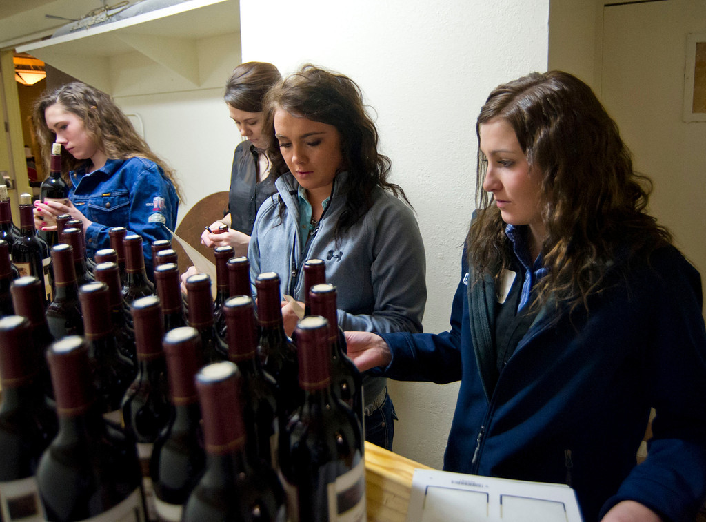 Rodeo students Casidy Mutchler, middle, and Cady Halverson, right, prepare wine bottles before the Sheridan College Rodeo Banquet Saturday evening at the Holiday Inn.
