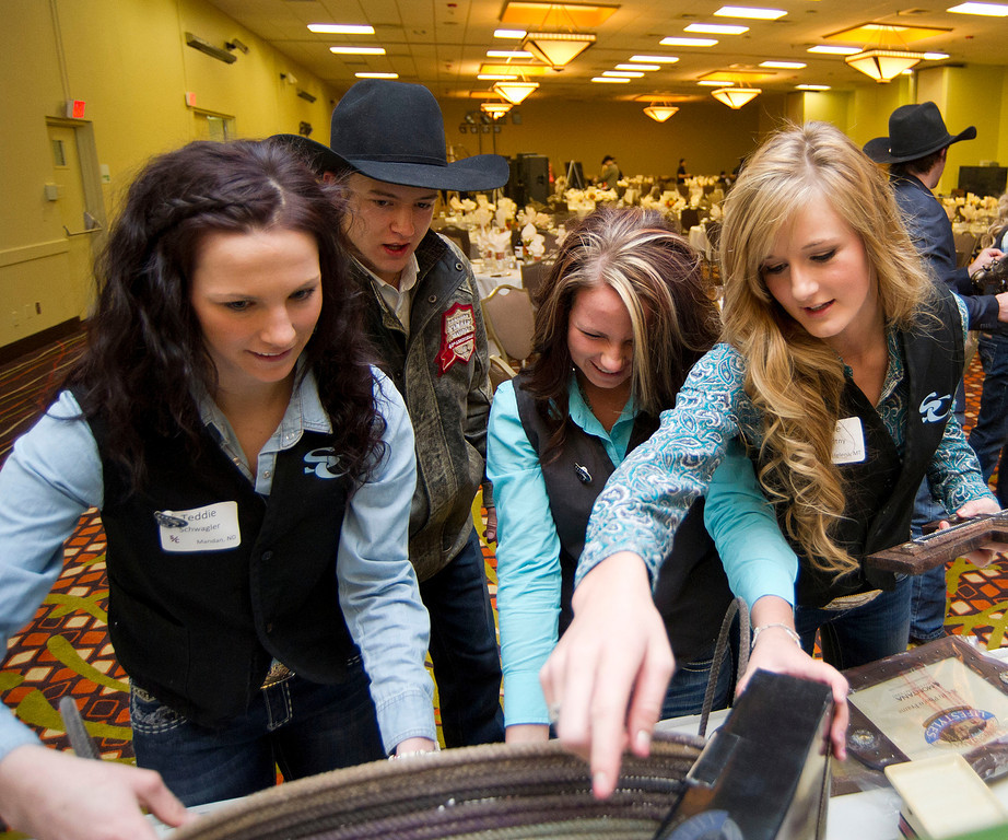 Opinions are shared as rodeo athletes crowd around a table to set up an auction item display in preparation of the fourth annual Sheridan College Rodeo Banquet Saturday evening at the Holiday Inn. Students pictured, from left, Teddi Schwagler, Zeke Thurston, Shelby Newman, and Allie Novotny.