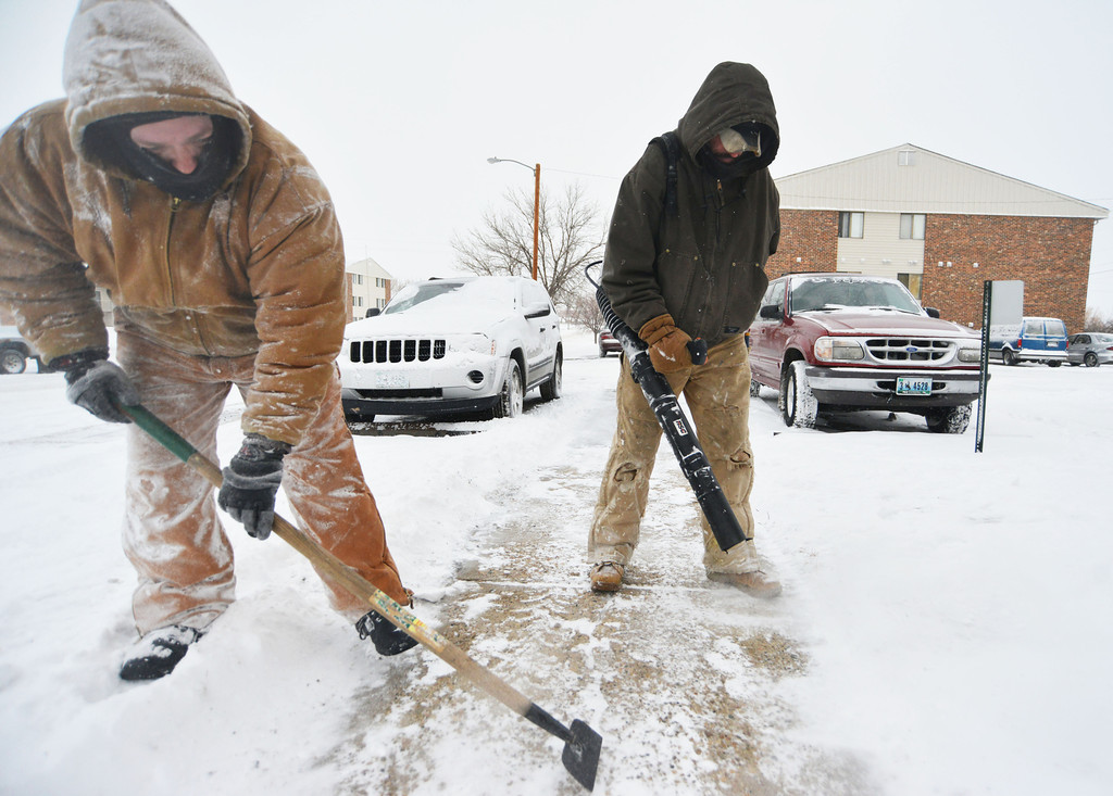Maintenance team Ron Schaal, left, scrapes off packed snow as Mat Mullikan operates a leaf blower to clear the paths at Country Club Estates Tuesday morning.