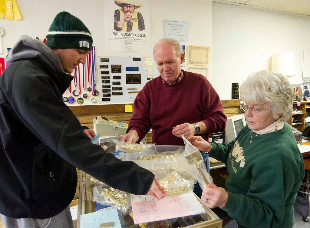 Customer Robbie Spencer, left, looks at an assortment of basketball trophy parts with owners Wade and Dianne Freiboth Thursday at The Trophy Case business on Main Street. Spencer ordered a number of trophies for The Sheridan Recreation District's Basketball League awards.