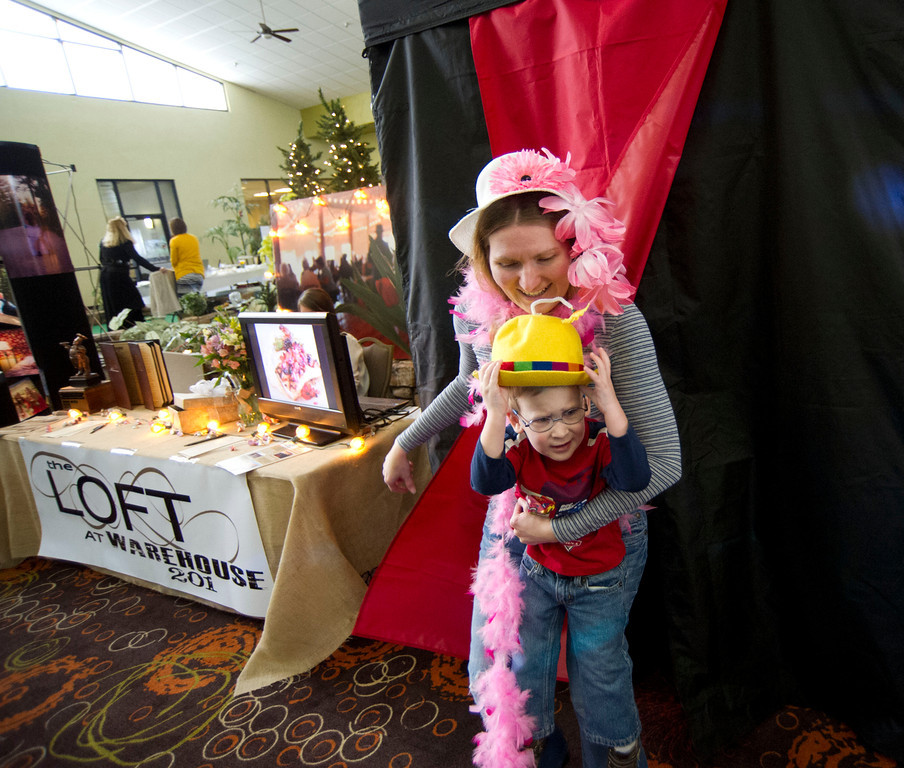 Mauriah Smith exits the photo booth as her 3-year-old son Silas Smith holds on to a prop during the Wyoming Weddings free bridal expo Saturday at the Holiday Inn atrium.