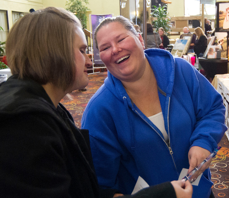 Alicia Hilleshiem, left, and Marci DeWitt react to their instant photos after visiting the 'Funky Fun Foto Booth' during the Wyoming Weddings free bridal expo Saturday at the Holiday Inn atrium.