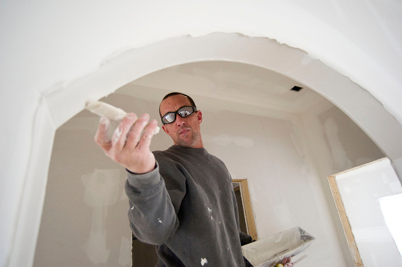 Philip Thompson with Excalibur Construction applies drywall mud to an arched doorway in a residential construction site Friday at the Bozeman Trail Estates west of Sheridan. The Sheridan Press/Justin Sheely