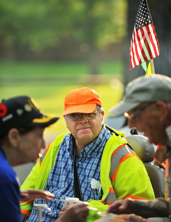 Robert Conley watches as an American Legion volunteer helps a visitor dress his meal during the Concert in the Park Tuesday at Kendrick Park. Post 7 was raising money to support the American Legion Boys and Girls Baseball teams and the Drum and Bugle Corps.