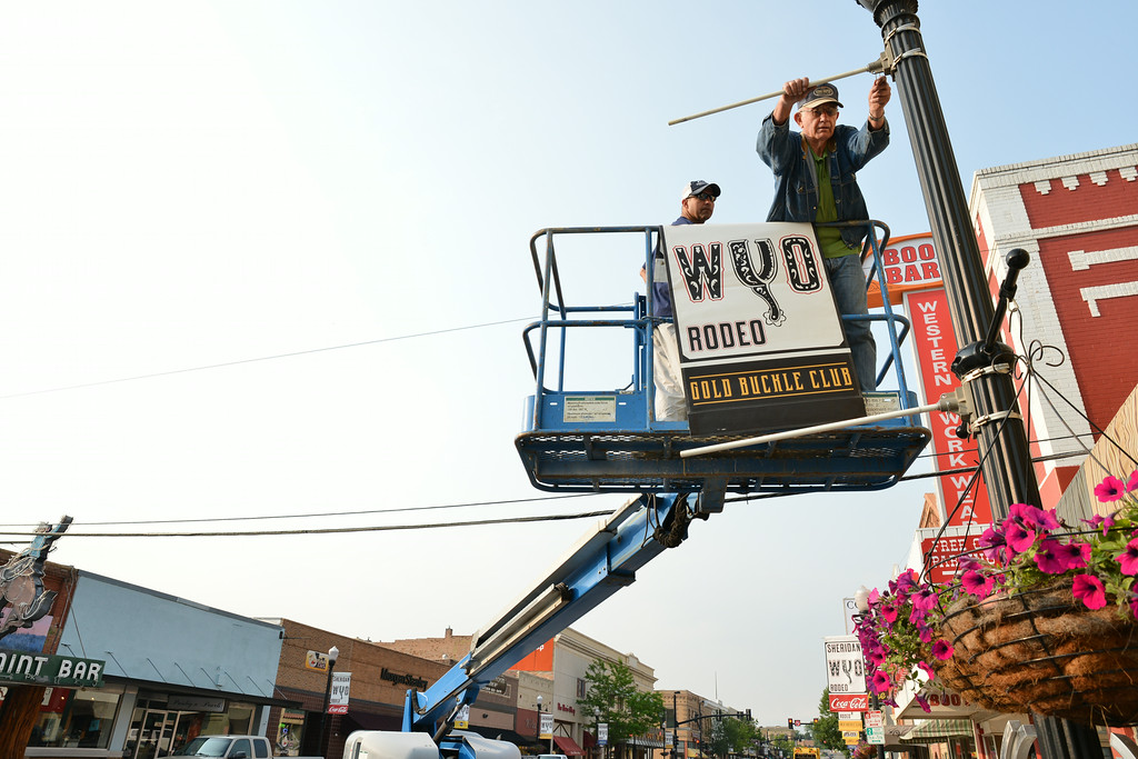 Rodeo volunteers Brad Walden, left, and Guy Fowler install a Sheridan-Wyo-Rodeo banner on a lamp post on Main Street in downtown Sheridan Tuesday morning. The volunteers had been working since 5 a.m. to work with minimal traffic. The Sheridan Press|Justin Sheely
