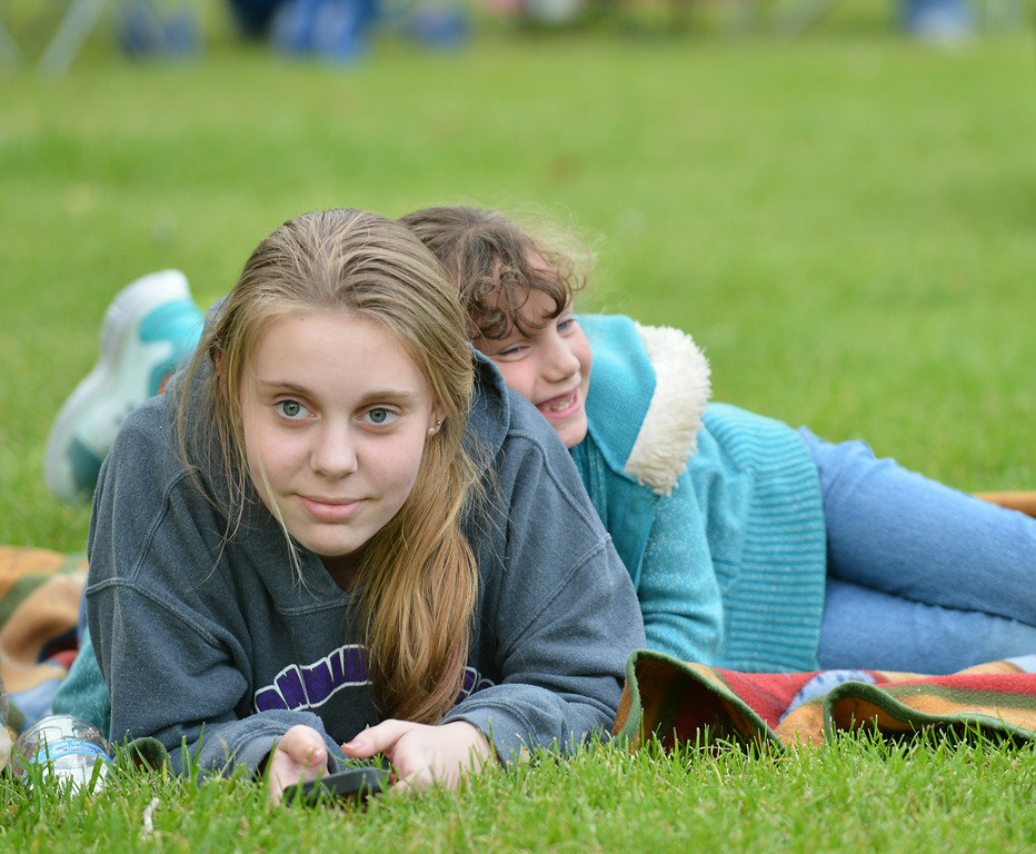 Thirteen-year-old Cassidy Lee of Texas, left, and cousin Sidney Herrigel of Sheridan, 7, listen to the Smokehouse performance during Concert in the Park Tuesday evening at Kendrick Park.
