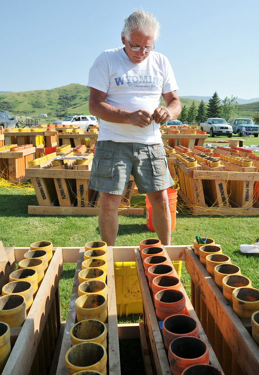 Ed Salvatore connects the wiring module for the fireworks shells during setup for the Fourth of July fireworks show Wednesday afternoon at the Big Horn Equestrian Center. Each mortar shell is fired according to a timed sequence set by the firing control computer. The fireworks display is timed to by choreographed with music that will be broadcasted over the air by local radio during the show. Bruce Burns with his crew of certified pyrotechnics and volunteers have been working all week to get ready for the popular fireworks display at the polo fields. The fireworks show will light up a 10 p.m. Friday night.