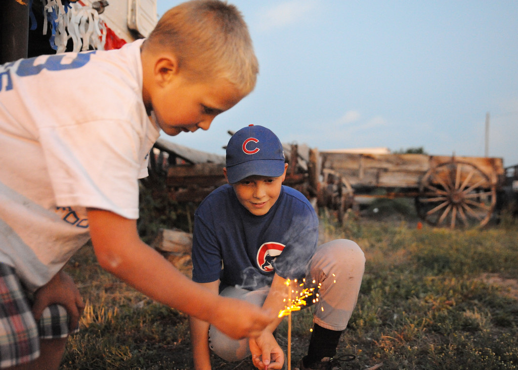 Seven-year-old Austin Geertz, left, and Nathan Geertz, 12, light little dynamites outside at the Whiz Bang Fireworks Tuesday night on the north end of Sheridan near Kmart.