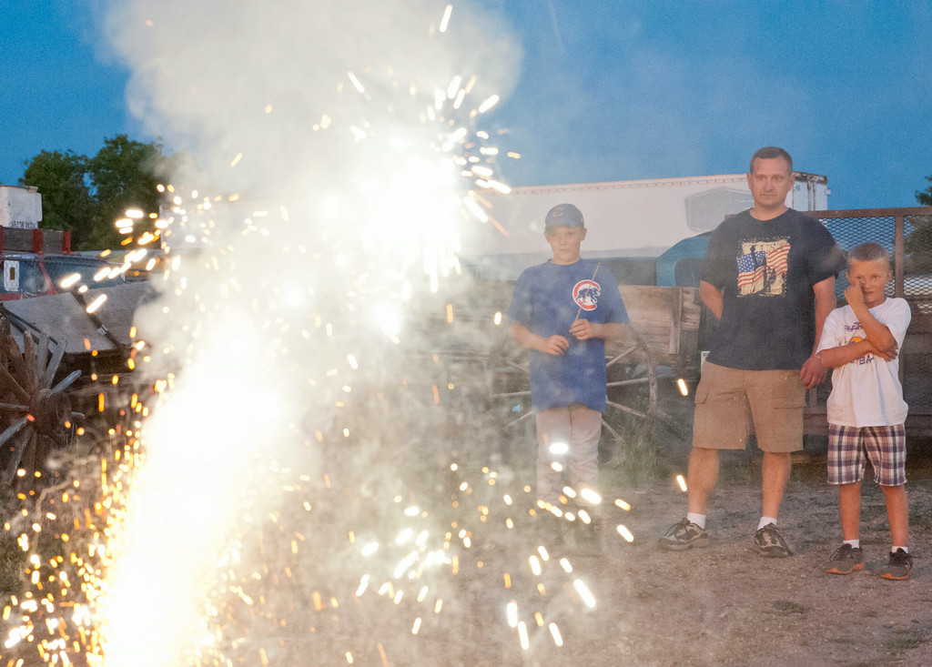 Nathan Geertz, left, Scott Dunham, and Austin Geertz watch a sparkling fountain light up outside at the Whiz Bang Fireworks Tuesday night on the north end of Sheridan near Kmart.