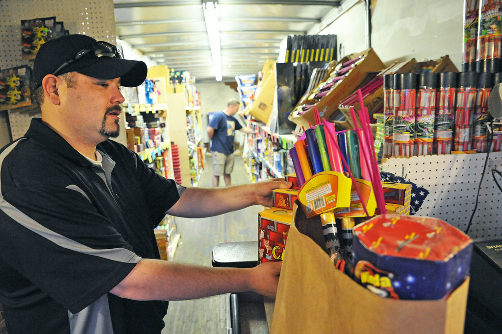 Jay Calentine purchases a load of fireworks at Whiz Bang Fireworks Tuesday night on the north end of Sheridan near Kmart. The locally owned family business has been operating in Sheridan for 39 years.