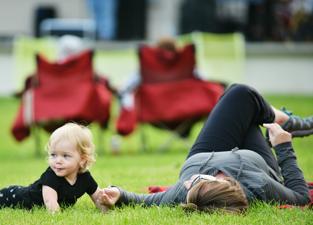 Eighteen-month-old Vivian Neeriemer and mother Theater Neeriemer lay in the grass during Concert at the Park Tuesday evening at Kendrick Park.