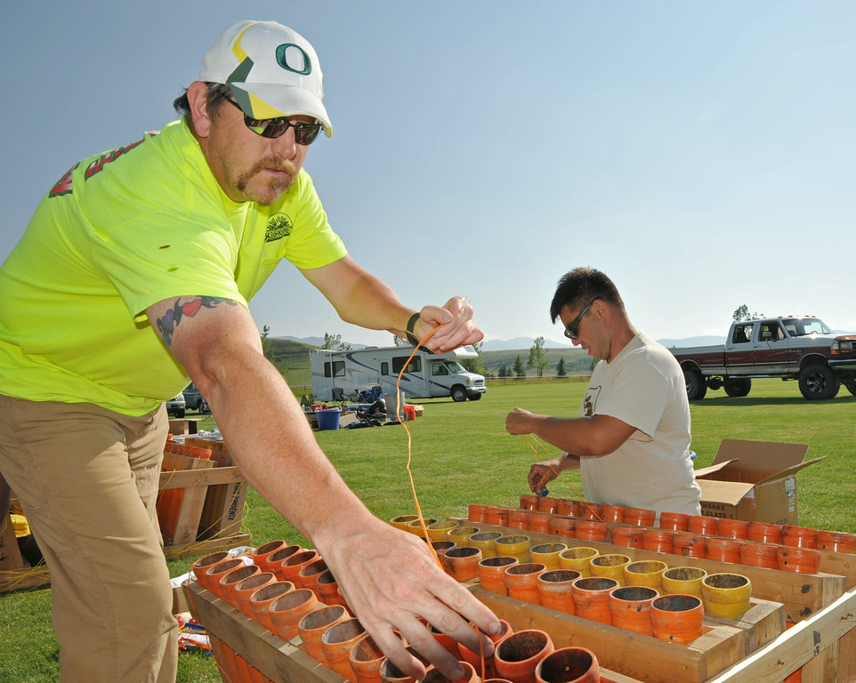 Dave Avery, left, and Justin Bishop load shells into three-inch mortars during setup for the Fourth of July fireworks show Wednesday afternoon at the Big Horn Equestrian Center. Each mortar shell is fired according to a timed sequence set by the firing control computer. The fireworks display is timed to by choreographed with music that will be broadcasted over the air by local radio during the show. Bruce Burns with his crew of certified pyrotechnics and volunteers have been working all week to get ready for the popular fireworks display at the polo fields. The fireworks show will light up a 10 p.m. Friday night.